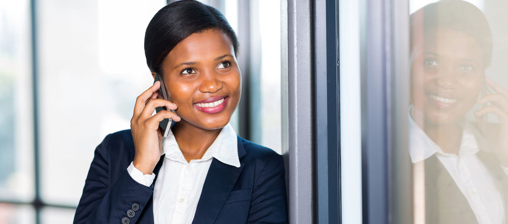 Young lady in business suit is smiling while talking on her cell phone.