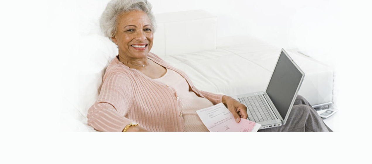 An older lady is sitting with her laptop in her lap smiling.