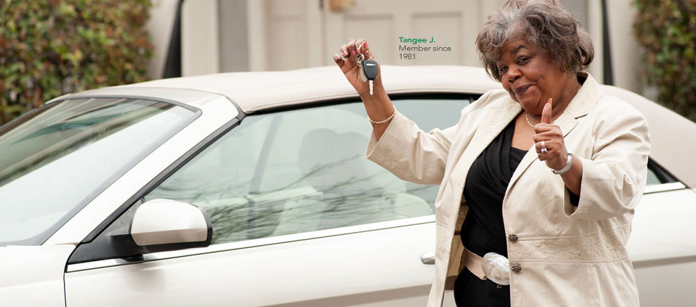 Member Tangee, is holding up a set of keys in front of her car and giving the thumbs up sign.