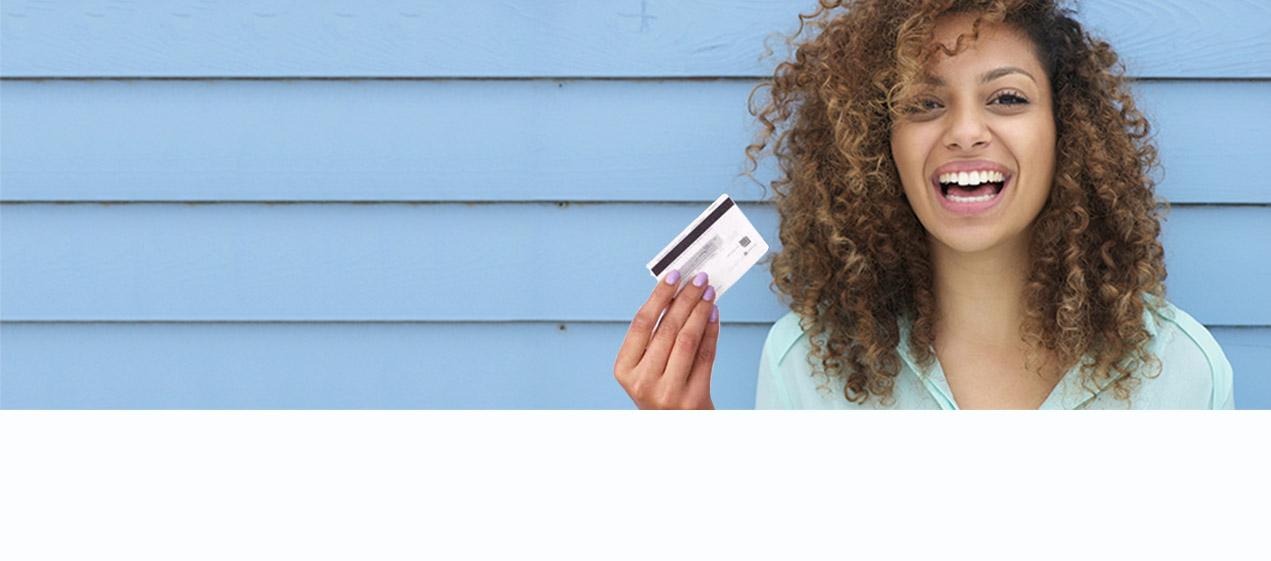 There's a young lady standing in front of a blue wall holding a debit card in her hand and smiling