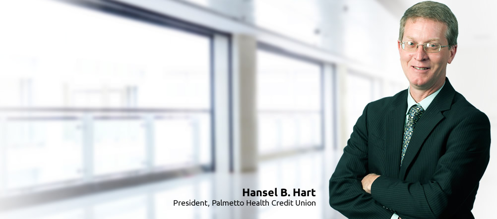 Palmetto Health Credit Union President, Hansel B. Hart, is smiling and standing with arms crossed.