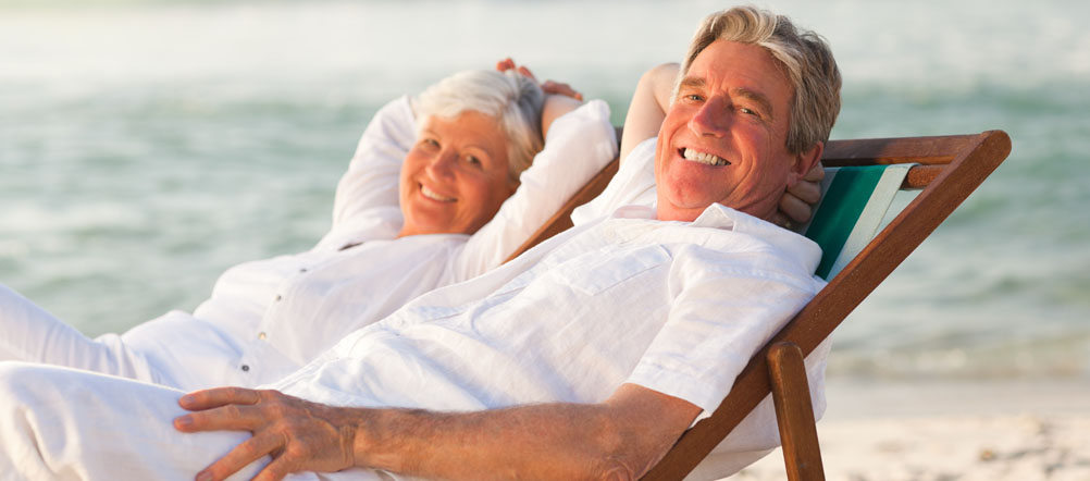 Retired couple dressed in all white is sitting in beach chairs smiling with the ocean behind them.