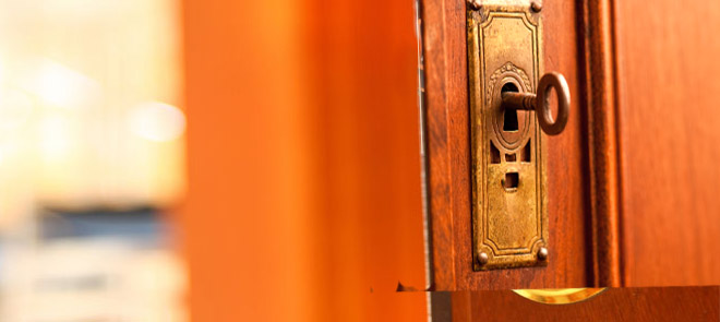 There's an old fashioned key in the lock of an open door.