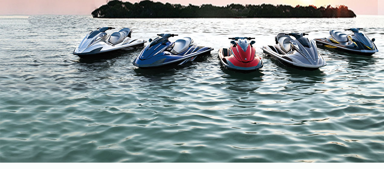 There's a group of jet skis lined up side by side in a lake with an island in the background.