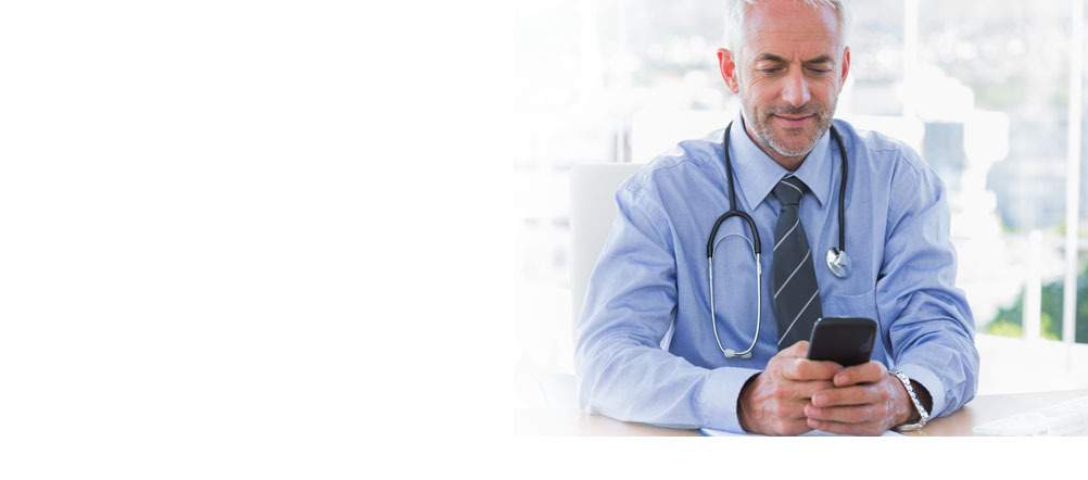 Man with stethoscope around his neck is sitting down looking at his cell phone.