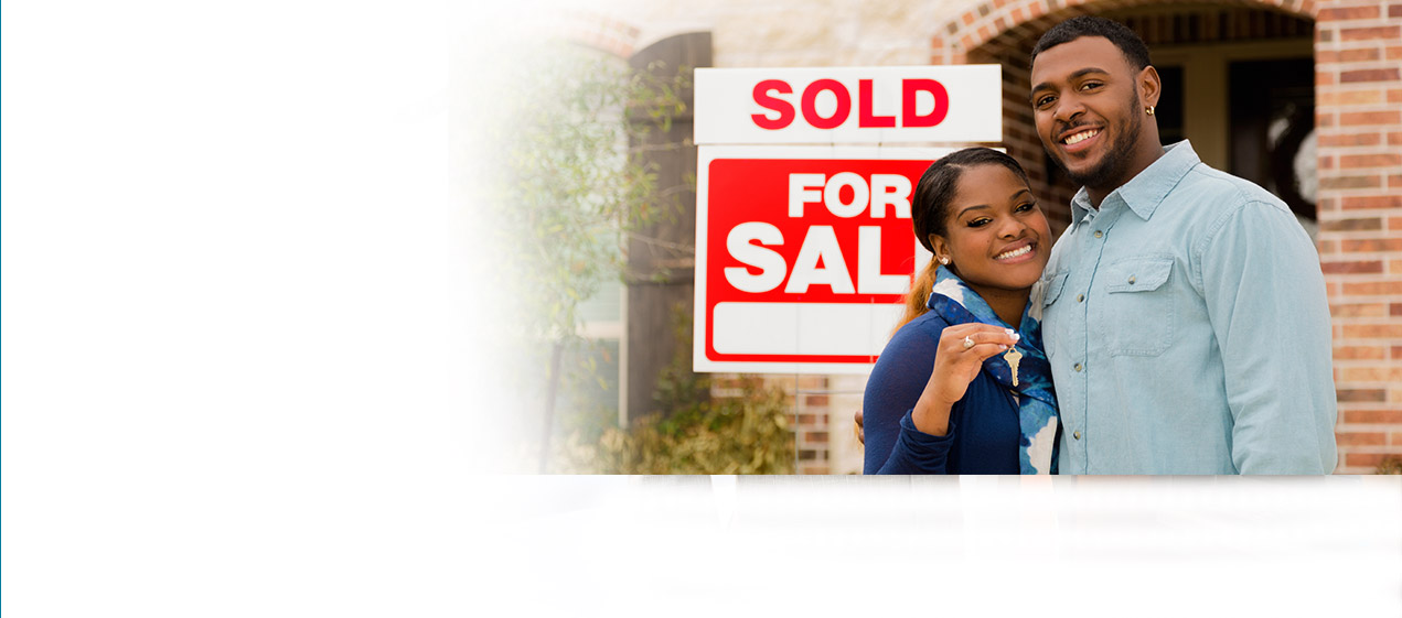 couple holding keys in front of For Sale sign